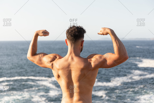 Back view of muscular male bodybuilder with strong naked torso demonstrating biceps while standing near sea in summer