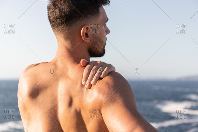 Back view of male bodybuilder with muscular naked torso warming up and stretching arms before workout near sea in summer