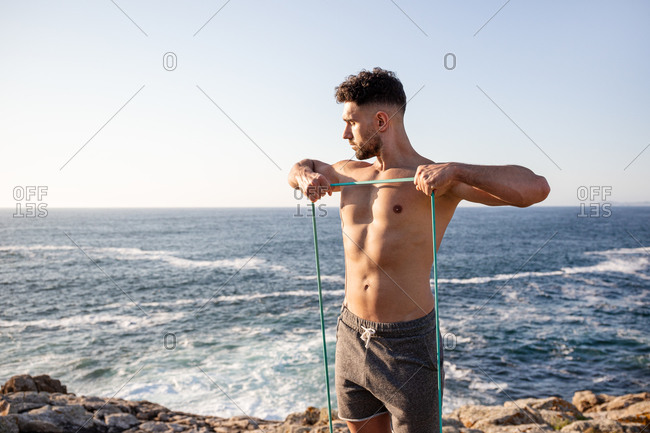 Muscular male bodybuilder with naked torso standing on seashore and doing exercises with resistance band during workout in summer
