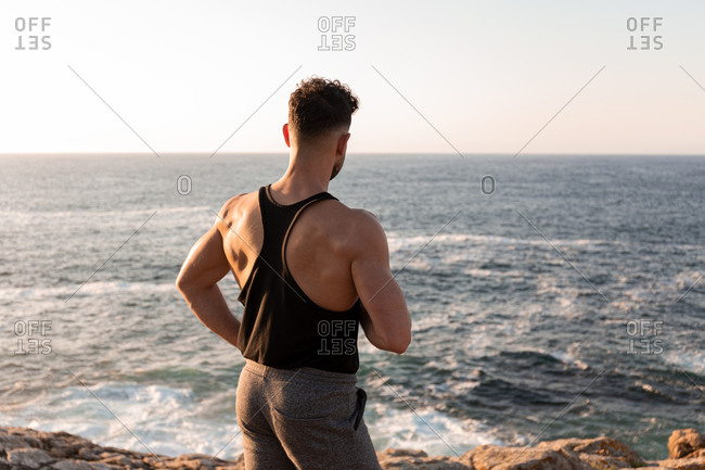 Back view of muscular male athlete in sportswear standing on beach and enjoying sundown after training in summer