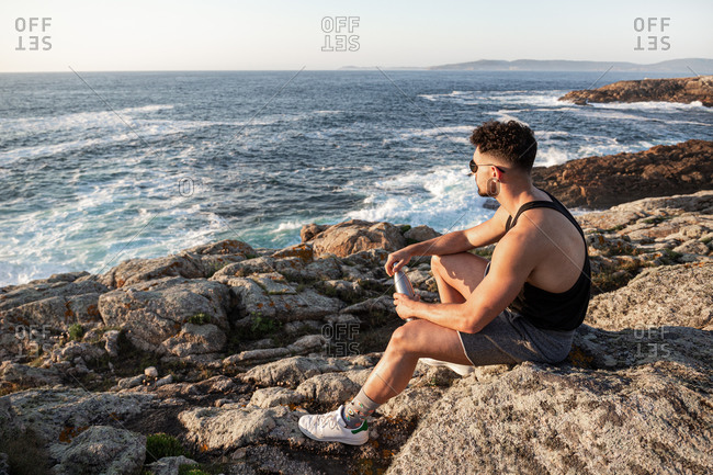 Side view of peaceful male sitting on rock on coast and admiring calm seascape at sundown in summer