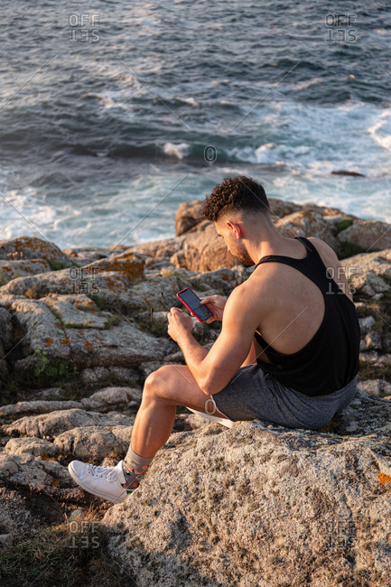 Side view high angle of male in summer clothes sitting on rock near sea and messaging on social media via cellphone at sunset