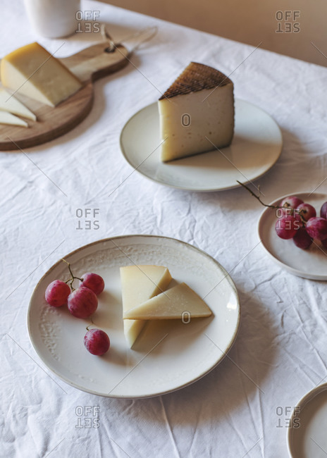 High angle of various palatable cheese arranged on table with Anona fruits and grapes near ceramic jug