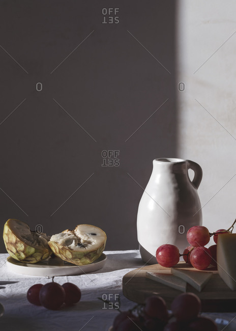 Ceramic jug placed on table with sweet fruits and delectable cheese in bright room lit by sunlight