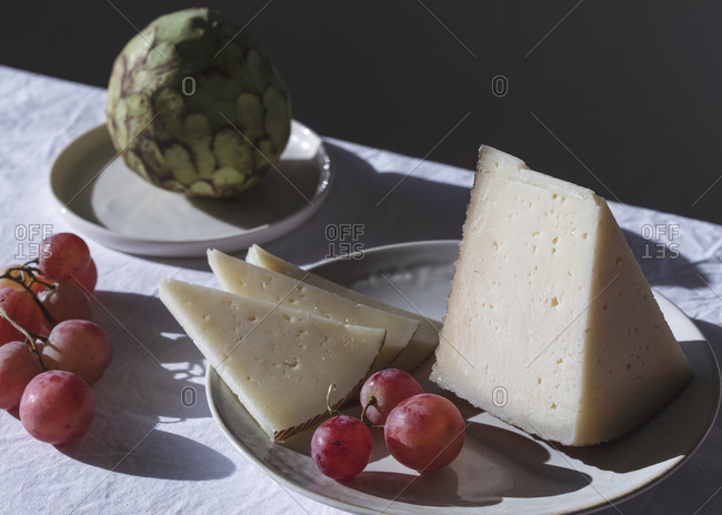 Table with sweet fruits and delectable cheese in bright room lit by sunlight