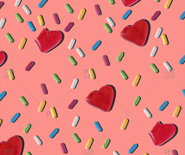 Top view of pattern of red heart shaped and colorful small jelly candies on pink background