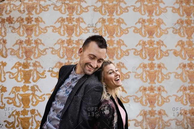 Side view of happy adult man and woman standing back to back and laughing against wall with vintage wallpaper