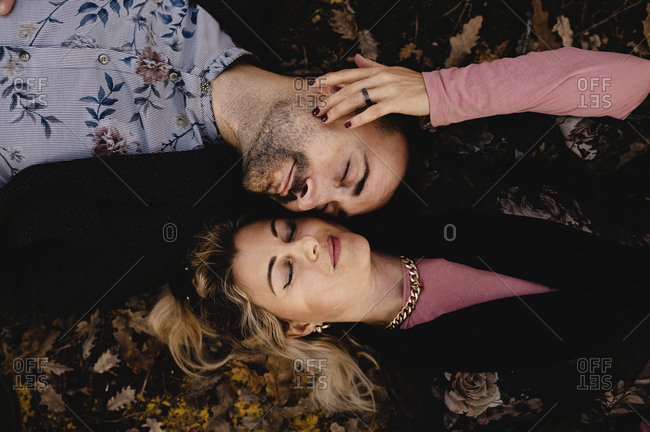 Top view of stylish relaxed romantic couple with eyes closed enjoying happy moments together while lying on dry leaves in autumn park