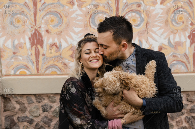 Loving adult man kissing cheerful woman while holding together cute fluffy dog near wall of old building