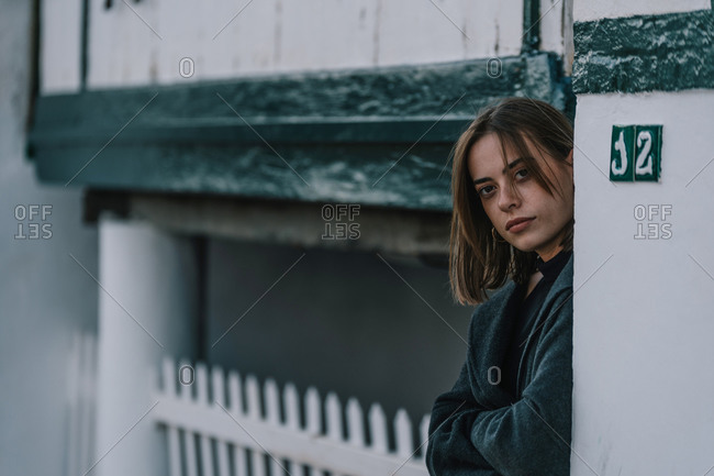 Emotionless female standing with crossed arms near old building and looking at camera on overcast day