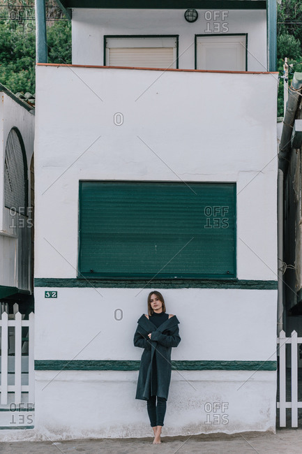Tranquil female in casual outfit leaning on wall of shabby building while looking at camera