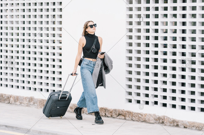Stylish female tourist with suitcase walking along street in city and looking away