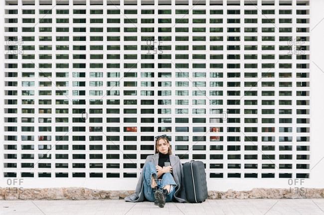 Female tourist with luggage sitting alone on pavement while getting lost in city looking at camera