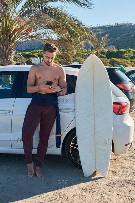 Fit male surfer standing near car with surfboard and browsing cellphone on sunny day