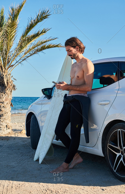 Fit male surfer standing near car with surfboard and browsing cellphone on sunny day on the seashore