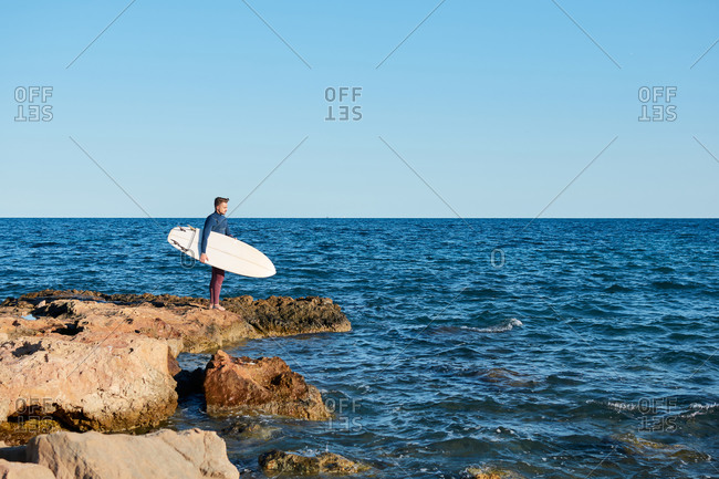 Side view of male surfer in wetsuit standing on rock near sea with surfboard and getting ready for surfing