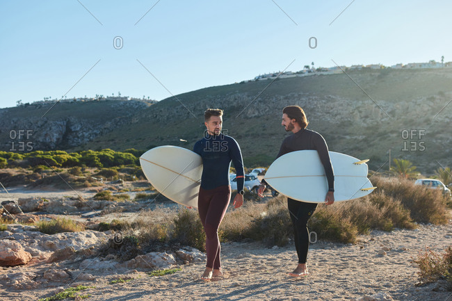 Positive male surfers in wetsuits and with surfboards walking along wet seashore after surfing at sunset
