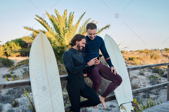 Delighted male surfers in wetsuits standing on wooden promenade with surfboards and browsing cellphone together