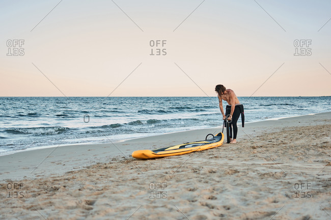 Man in wetsuit inflating paddle board at the seashore on sandy beach