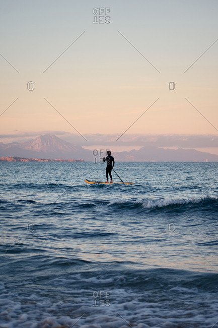 Male surfer in wetsuit rowing on paddle board on sea water on background of mountains at sunset
