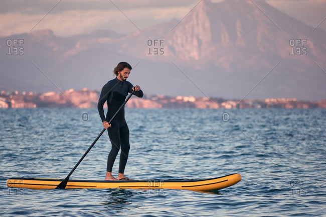 Side view of male surfer in wetsuit rowing on paddle board on sea water on background of mountains at sunset
