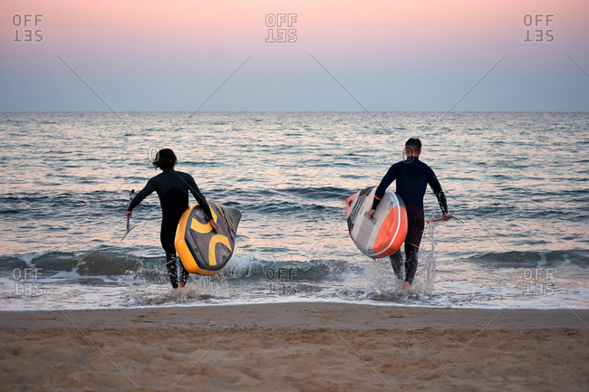 Back view of unrecognizable male surfers in wetsuits caring paddleboards to the sea