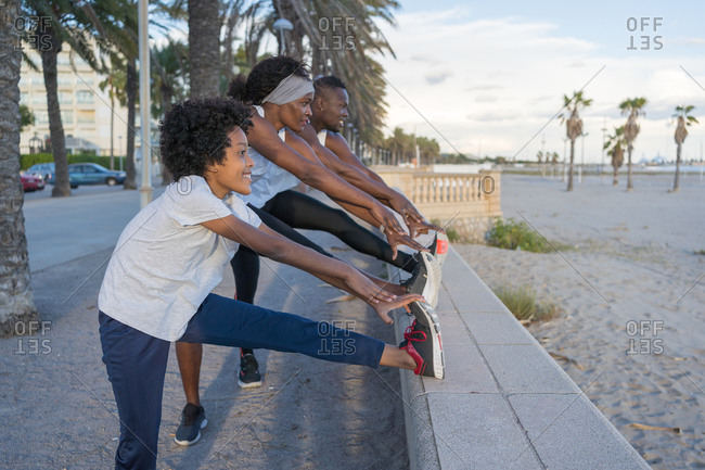 Side view of flexible African American couple and teenager training together and warming up legs on embankment in summer while looking away