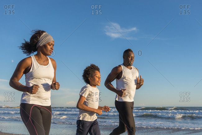 African American family in sportswear running along sandy beach near sea and training together at sunset in summer