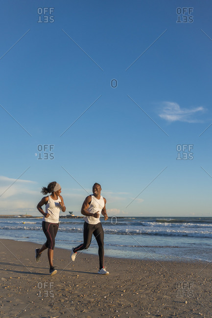 Side view of African American sportspeople running together during workout on sandy beach near sea