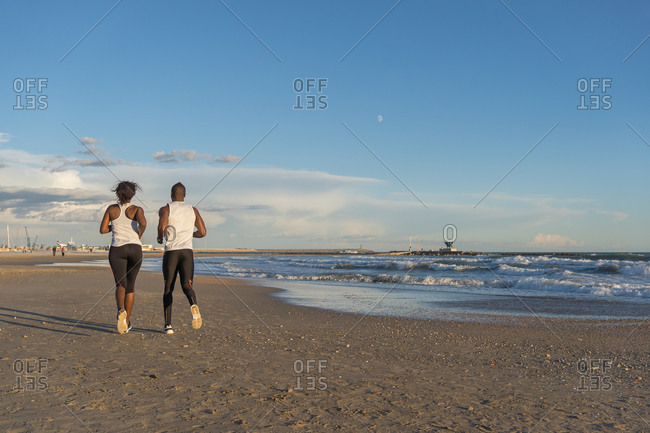 Back view of African American sportspeople running together during workout on sandy beach near sea