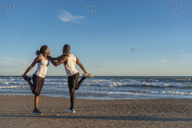 Side view of African American sportspeople leaning on each other and stretching legs before workout on sandy beach near sea