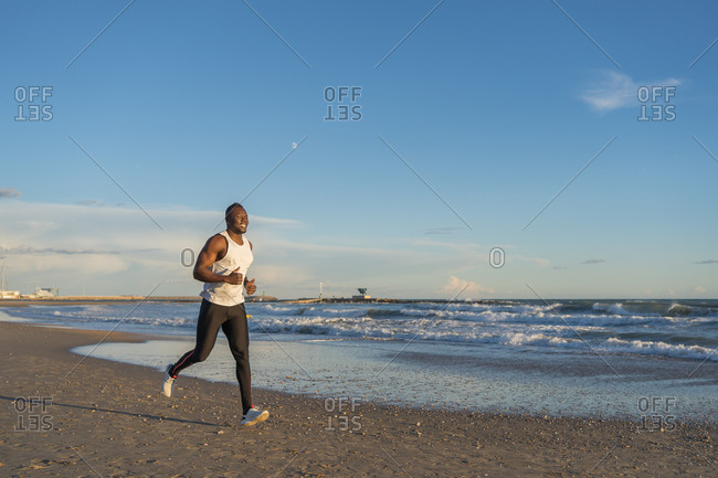 Smiling African American male athlete in sportswear running along seashore and enjoying sunset over sea in summer