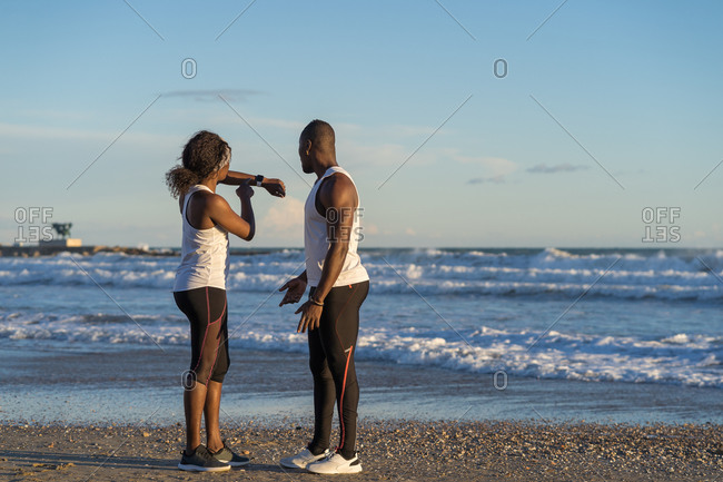 African American sportspeople looking at smartwatch before workout on sandy beach near sea