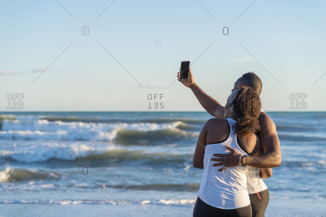 Black couple of athletes in activewear standing on sandy shore and taking selfie on smartphone while hugging after active training