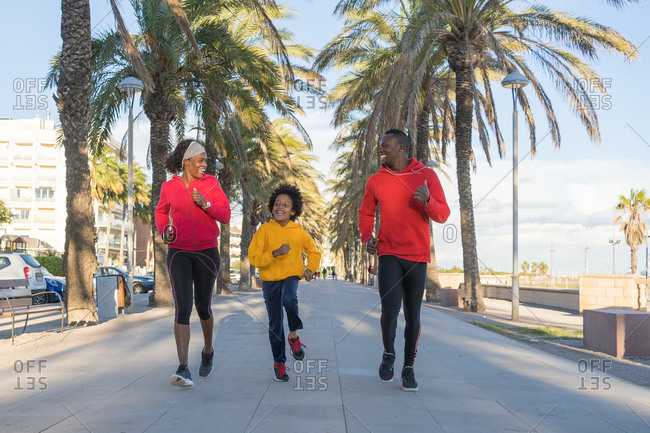 African American family in colorful sportswear running along street while smiling and training together in summer