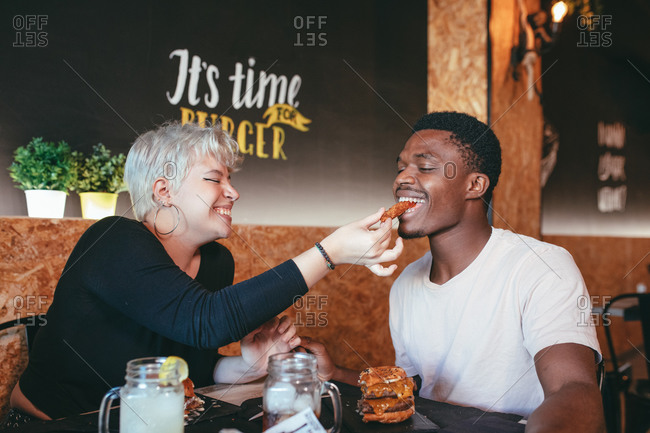 Cheerful woman and black male friend sitting in fast food cafe having fun while eating burgers
