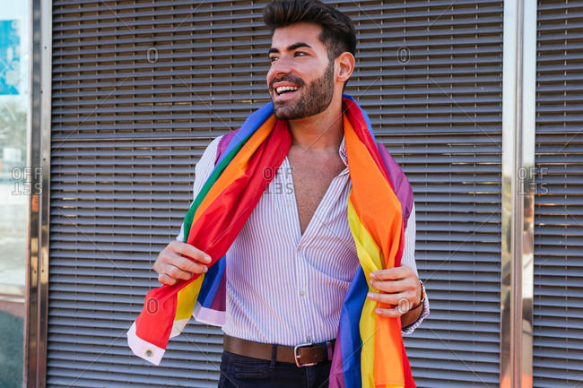 Positive gay male standing with rainbow LGBT flag wrapped around neck in city and looking away