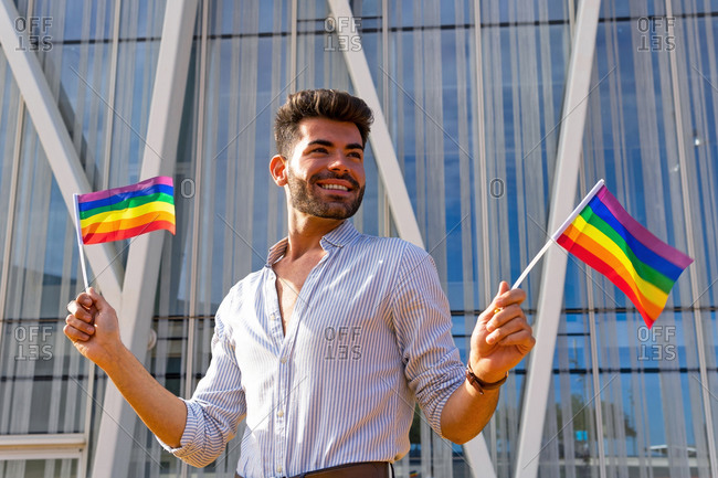 Low angle of delighted homosexual male standing on street with paper LGBT flags and looking away
