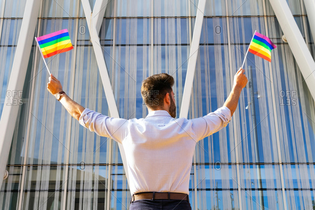 Back view low angle of homosexual male standing on street with paper LGBT flags and looking away