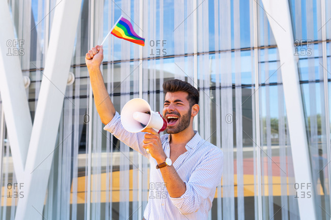 Side view of eccentric gay male with rainbow LGBT flag standing in city and yelling in loudspeaker with closed eyes