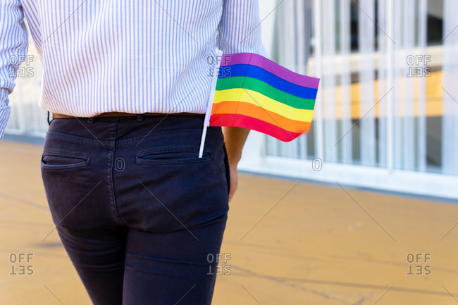 Back view of anonymous homosexual male walking along street with rainbow LGBT paper flag