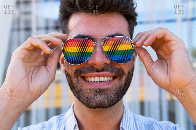 Delighted gay male putting on colorful sunglasses with rainbow LGBT flag and looking at camera