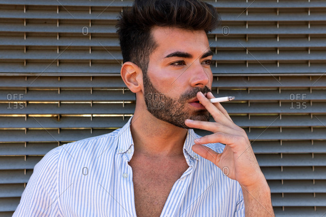 Thoughtful handsome male leaning on building and smoking cigarette in city while looking away in contemplation