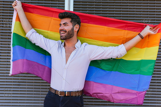 Positive gay male standing with rainbow LGBT flag in city and looking away