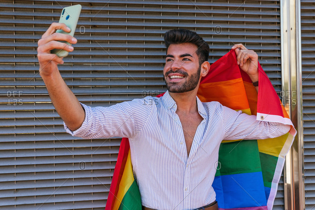 Content homosexual male taking self portrait with rainbow LGBT flag while using smartphone and standing near building in city