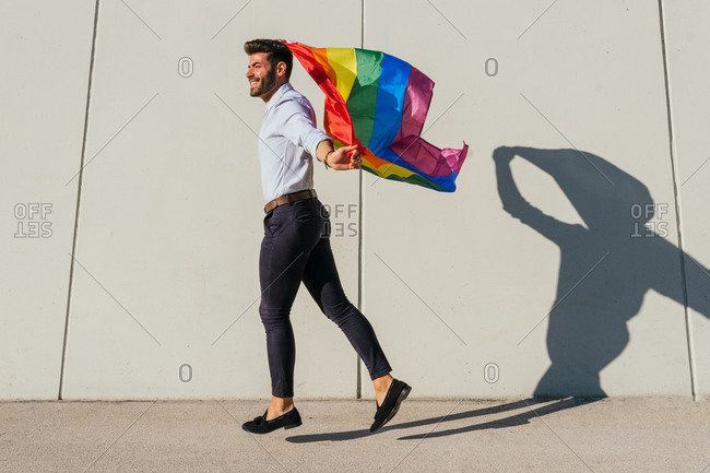 Side view of cheerful homosexual male in moment of jumping with rainbow LGBT flag on city street on sunny day