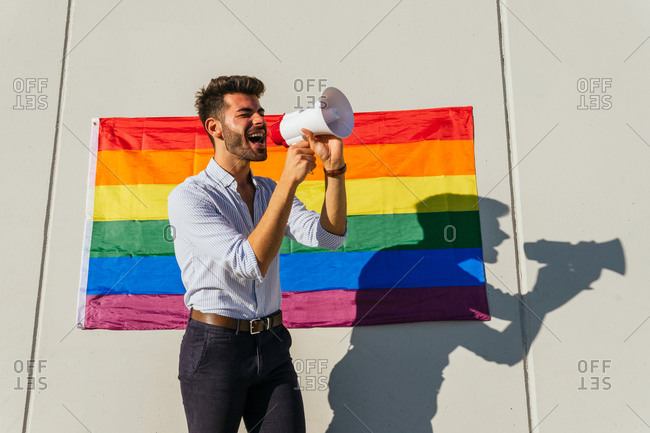 Side view of excited homosexual male standing near building with LGBT rainbow flag and shouting in loudspeaker