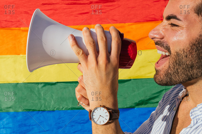 Cropped side view of excited homosexual male standing near building with LGBT rainbow flag and shouting in loudspeaker