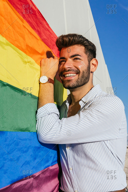 Glad homosexual male leaning on wall with rainbow LGBT flag and looking away with optimism