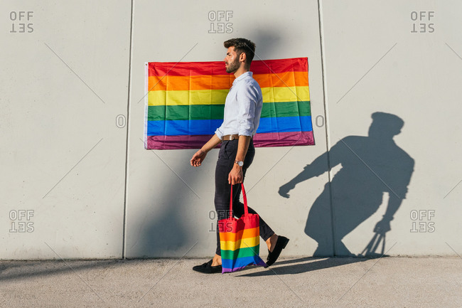 Side view of confident homosexual male with shopping bag in colors of LGBT rainbow flag walking in city and looking away